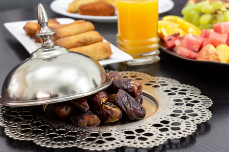Dried date Medjool palm fruits, fresh orange juice, samosa snack, spring roll and fruit background concept iftar buffet table Ramadan.