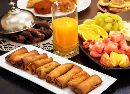 Iftar buffet. Spring roll, fruits, fresh orange juice, samosa snack, spring roll and pancake background concept iftar holy month Ramadan. Stock Photo