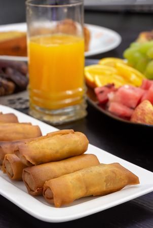 Iftar Buffet table. Spring roll, fruits, fresh orange juice, samosa snack, spring roll and fruit background concept iftar in the holy month Ramadan.