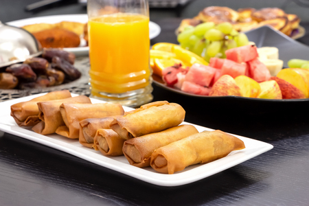 Iftar buffet table. Spring roll, fruits, fresh orange juice, samosa snack, spring roll and pancake background concept iftar holy month Ramadan.