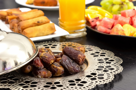 Dried organic dates palm fruits, fresh orange juice, samosa snack, spring roll and fruit background concept iftar in the holy month Ramadan.