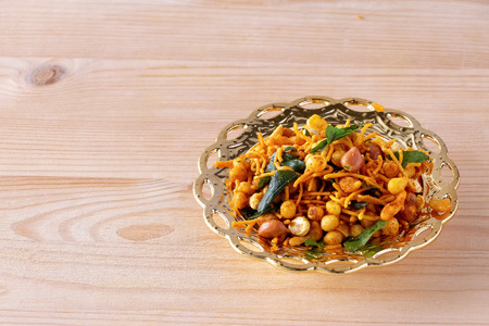 South indian spicy crunchy mix Nimco or Namkeen with peanut, rice, curry leaves and spice golden bowl background isolated.