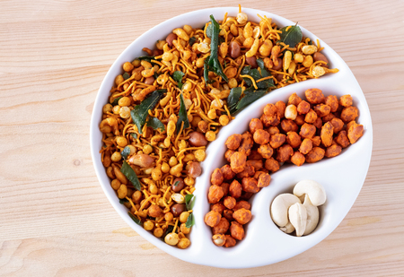 South indian spicy crunchy mix Nimco or Namkeen and spicy coated peanut white bowl wooden background isolated.