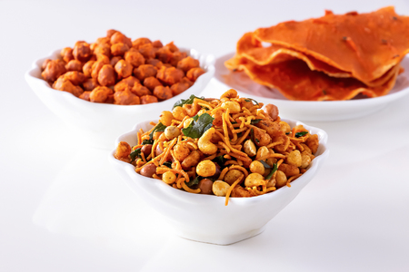 Assortment salty crunchy indian mix Nimco or Namkeen, spicy coated peanut and pappadam white bowl wooden background.
