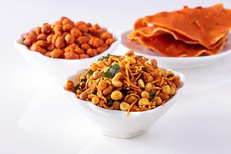 Sortiment salzige knusprige indische Mischung Nimco oder Namkeen, würzig beschichtete Erdnuss und Pappadam weiße Schüssel Holzhintergrund. Standard-Bild