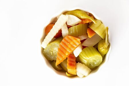 Verschiedene Essiggurken Gemüse Karotte, Chili, Rettich in weißer Keramikschale. Ansicht von oben. Isoliert. Platz kopieren. Ansicht von oben. Standard-Bild