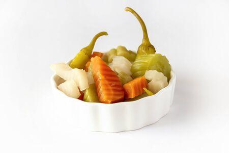 Assorted pickles vegetables carrot, chili, radish in white ceramic bowl.