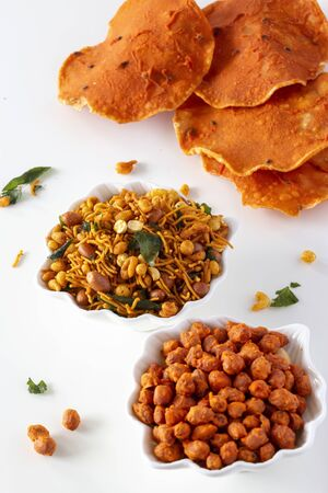 Pappad with black cumin and South indian spicy crunchy mix Nimco or Namkeen with peanut, rice, curry leaves and spice white bowl background isolated. Top view.