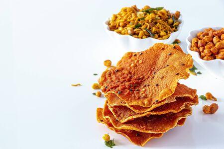 Pappadum Südindische würzige knusprige Mischung Nimco oder Namkeen mit Erdnuss, Reis, Curryblättern und weißem Hintergrund der Gewürzschale isoliert.