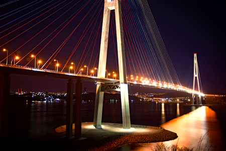 beautiful night city lights. high bridge across the Bay stretched on pylons. in water reflected glare from the bridge Stock Photo