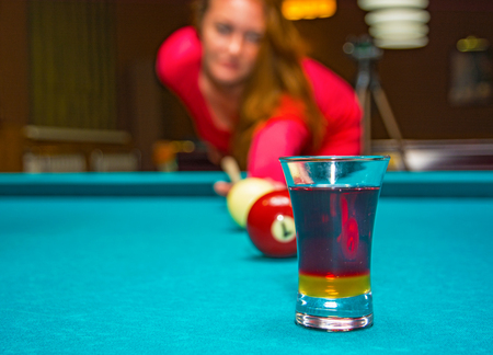 girl playing pool, has the ball and is reflected in the glass. billiard Club