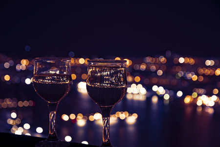 corridors: beautiful night scenery, goblets with drink stand in the background of the city at night, and the bridge with lights