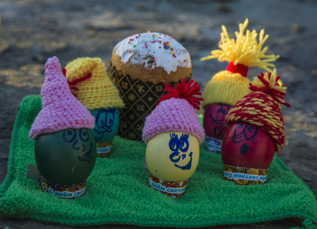 Easter eggs in caps, with funny faces in nature. Easter holiday