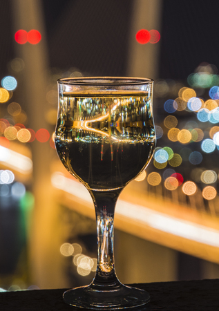 electric material: beautiful night scenery, goblets with drink stand in the background of the city at night, and the bridge with lights