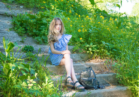 young beautiful girl sitting on the stairs in the park with flower, young beauty with long hair