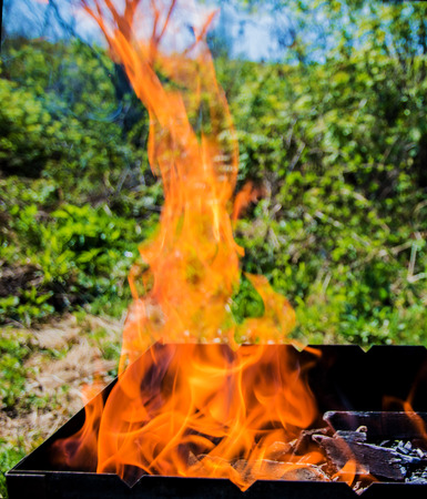 open flame, a bright red flame on the outdoors on a sunny day Stock Photo