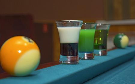 Sur un support de table de billard avec des verres colorés d'alcool. Billard, balles et empilement