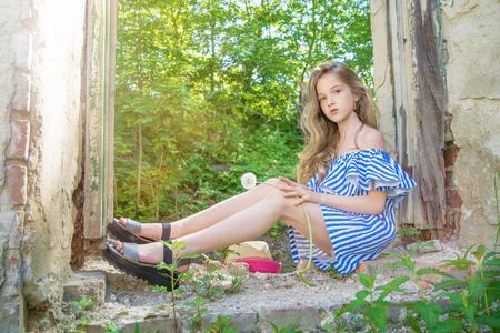 een jong meisje zit in de raamopening, in het verwoeste gebouw in het Park, portret van een jonge schoonheden
