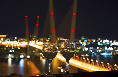 pedestrian bridge: beautiful night scenery, goblets with drink stand in the background of the city at night, and the bridge with lights