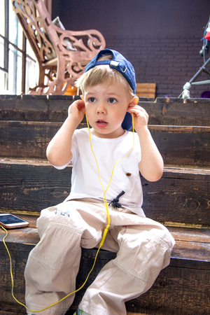 cute guy: the child plays with headphones, listening to music from your phone. sitting in a room on the stairs Stock Photo