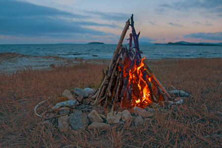 fire burning on the beach at night. bright fire, firewood. flame overnight Stock Photo
