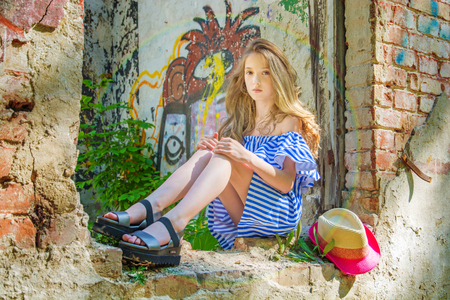 a young girl is sitting in the window opening, in the devastated building in the Park, portrait of a young beauties Stock Photo