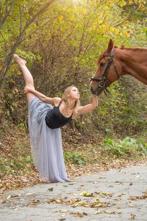 Jonge mooie danseres, poseren met een paard in het bos, flexibele turner. in het bos Stockfoto - 94769179