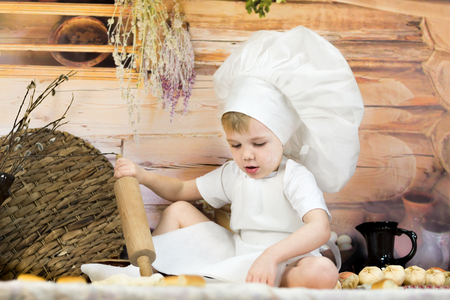 the little boy is preparing cake and pancakes. Dressed like a chef child dough prepares food. wooden house and Pancake week