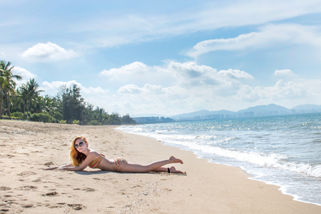 beautiful girl in bikini posing on a deserted beach. white sand, turquoise sea and a young girl. with a sunny day