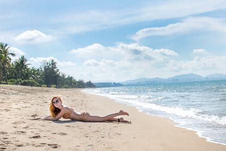 belle fille en bikini posant sur une plage déserte. sable blanc, mer turquoise et une jeune fille. avec une journée ensoleillée Banque d'images