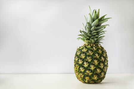 un intero ananas maturo si erge su una superficie bianca con uno sfondo grigio chiaro.