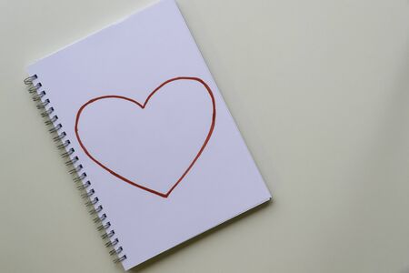 Drawing heart. With red felt-tip pen on a white sheet in a notebook.