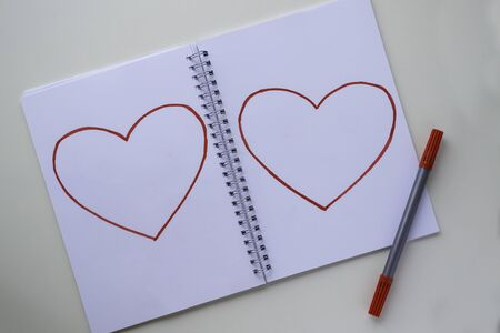 Hearts drawn by a red felt-tip pen on a white sheet in a notebook. The felt-tip pen lies nearby.