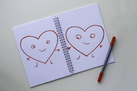 Hearts drawn by a red felt-tip pen on a white sheet in a notebook. Hearts with arms, legs and eyes.