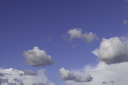 White cumulus clouds on blue sky.