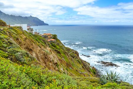 View of Benijo village, Canary island, Spain. The town in the north of Tenerife. Mountain green landscape and the ocean coast.