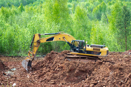 Clay mining. The yellow excavator digs red clay with a large bucket.