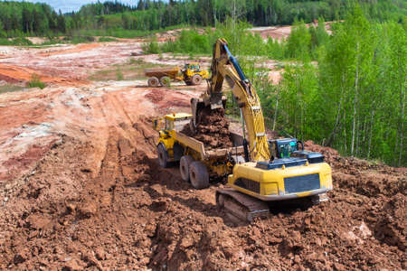 Clay mining. The yellow excavator digs red clay with a large bucket and puts it into the truck.