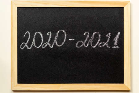 Back to school and new academic year concept. Blackboard with text 2020-2021 in wooden frame.