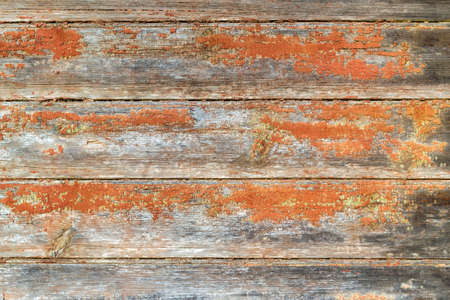 Aged dilapidated wall. Brown or red orange boards. Old, cracked and peeled paint. Rustic background. Place for text, copy space.
