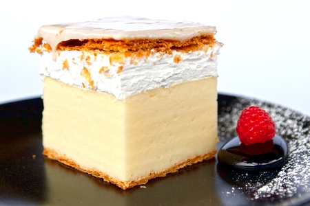 Creamy cake on black plate photo
