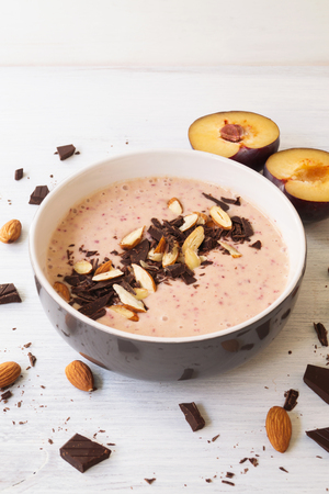 Plum chocolate almond smoothie bowl. Healthy smoothie breakfast, selective focus, vertical Stock Photo
