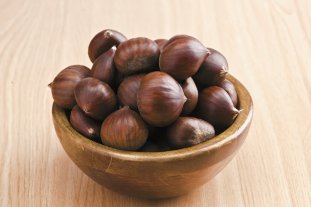 dark wooden bowl with chestnuts. wood-based photo