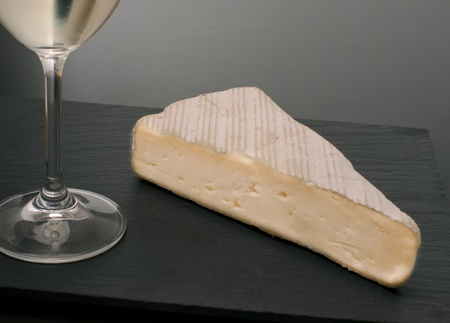 portion of brie cheese with white wine, dark stone on base photo