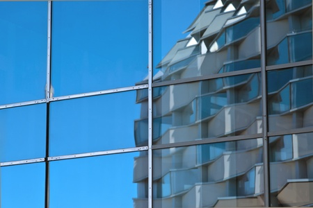 building reflected in the glass facade of another building photo