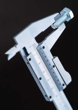 holding a screw gauge, in blue, with selective focus photo