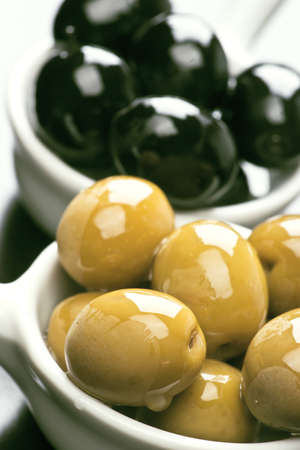 Black and green olives, sprinkled with oil on glossy dark base photo