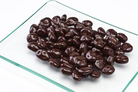 chocolate-covered raisins on transparent tray