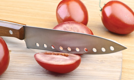 tomatoes cut by a kitchen knife on a wooden board, photo