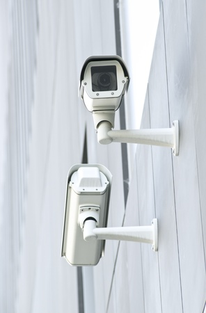 two surveillance cameras on the wall of a public building photo